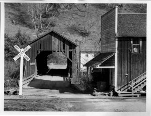 Taken by Ben Maxwell in 1955 we see the George Smith Store and Telephone Office in the foreground. The covered bridge, and behind both the Pepin Grocery Store.